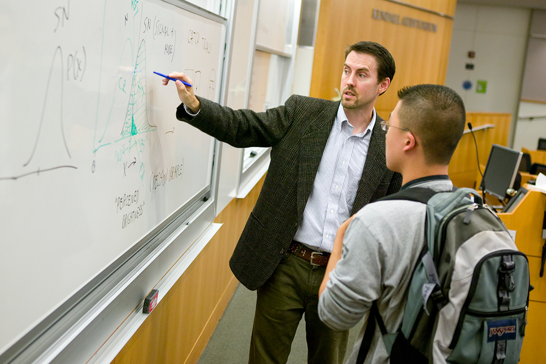 student and professor standing at a white board